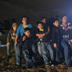 A group of immigrants from Honduras and El Salvador who crossed the U.S.-Mexico border illegally are stopped in Granjeno, Texas, in June. (Eric Gay / Associated Press )